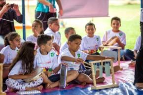Crianças brincando com instrumentos musicais reciclados.